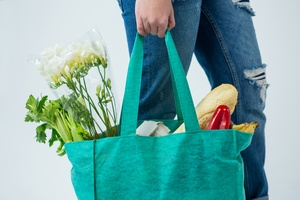 Mid section of woman carrying grocery bag against white background