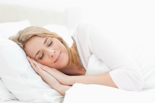 Woman sleeping in bed, hands positioned beside her face