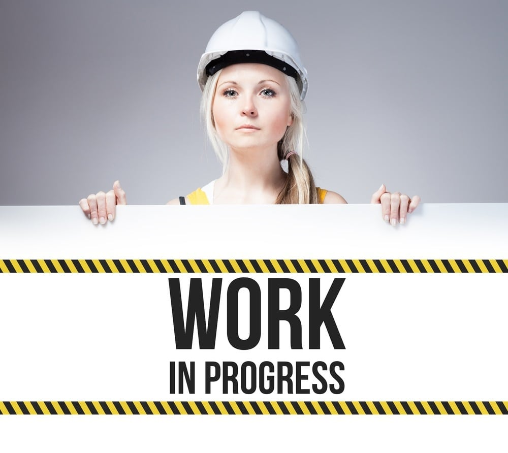 Worker holding work in progress sign on information board