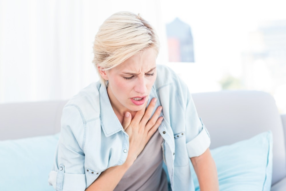 Pretty blonde woman having breath difficulties in the living room