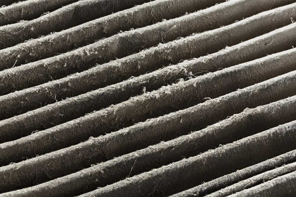 Close up dirty car air conditioner filter isolated on white