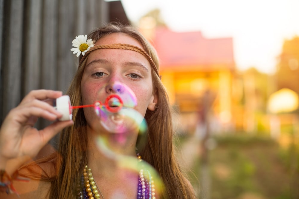 Young lovely hippie girl blow bubbles outdoors in village.