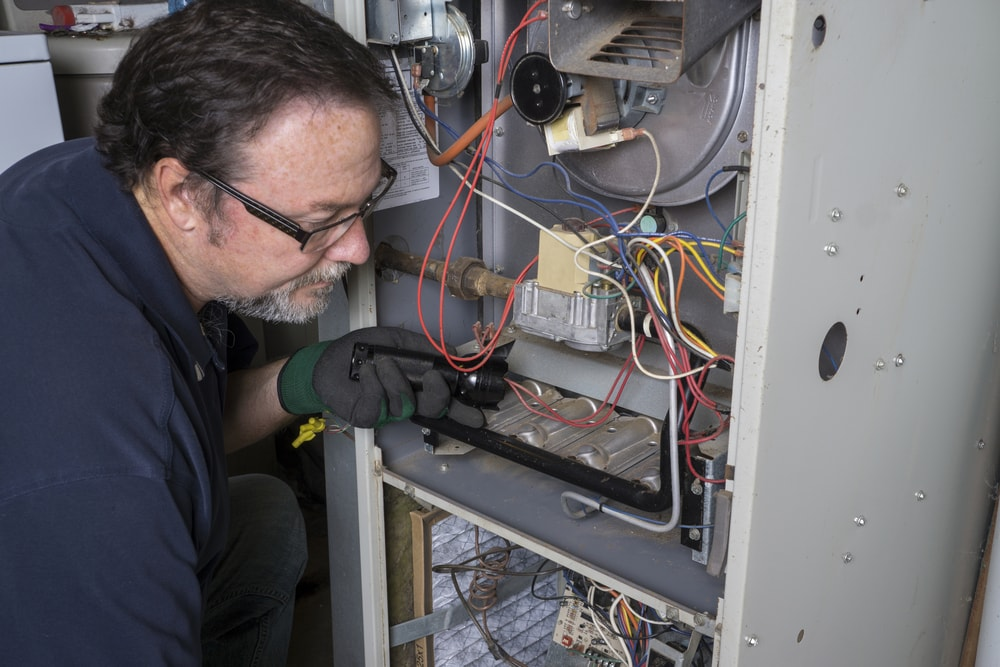 Techician looking over a furnace with a flashlight before cleaning it.