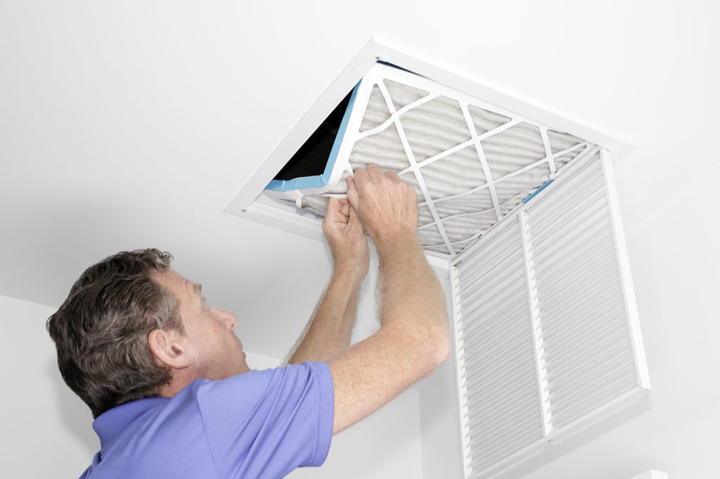 Mature man taking out a dirty air filter from a home ceiling air return vent. Male removing a dirty air filter with both hands in a house from a HVAC ceiling air vent.