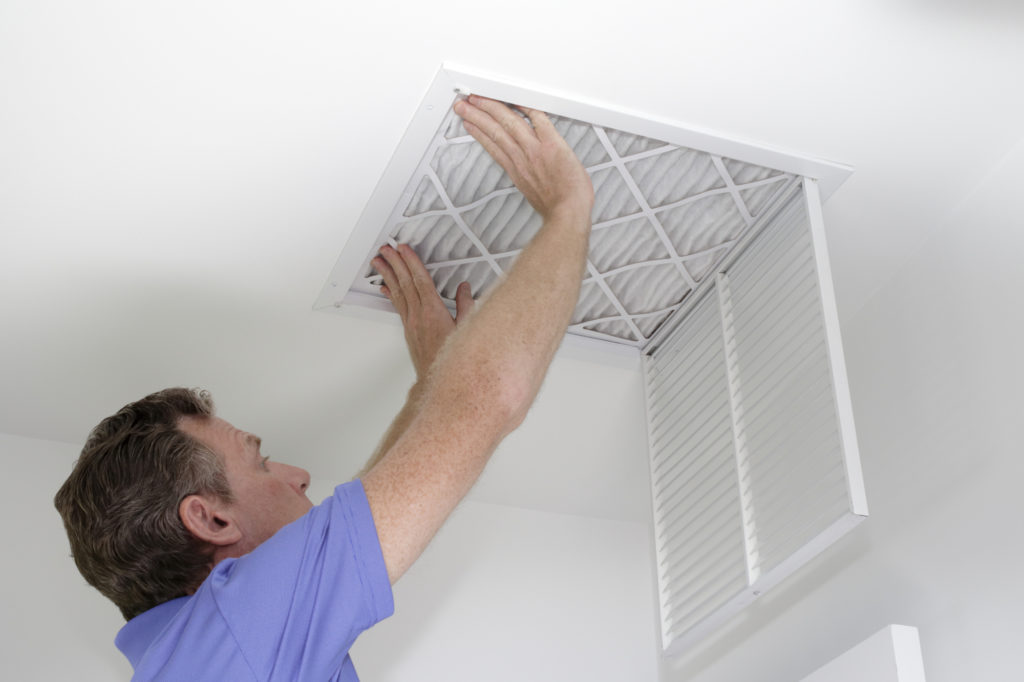 Male pushing a clean air filter into place in the ceiling with both hands. One fresh furnace air filter being secured in the intake grid of the white home ceiling.