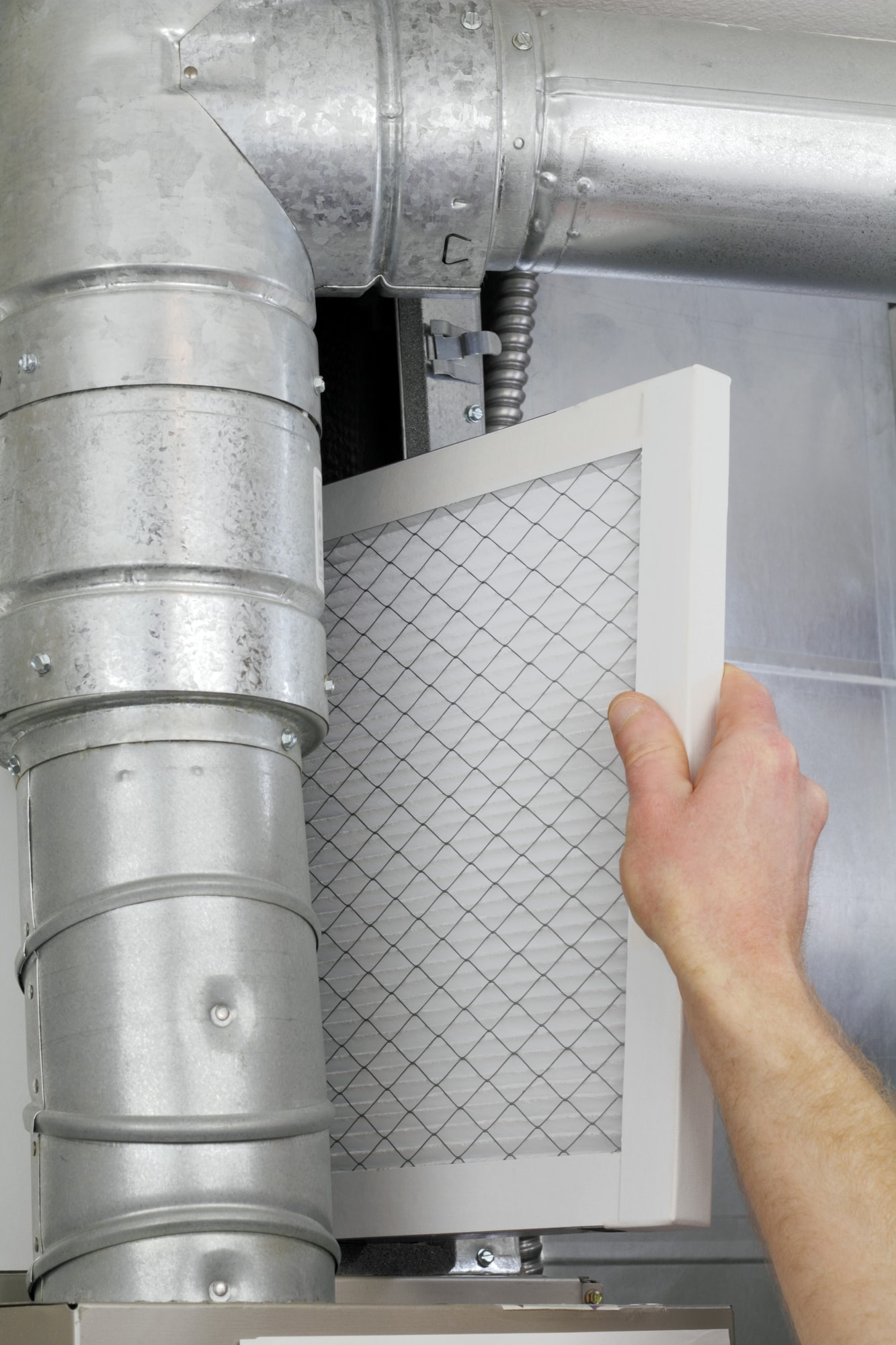 A man's arm and hand seen replacing disposable air filter in home central air furnace.