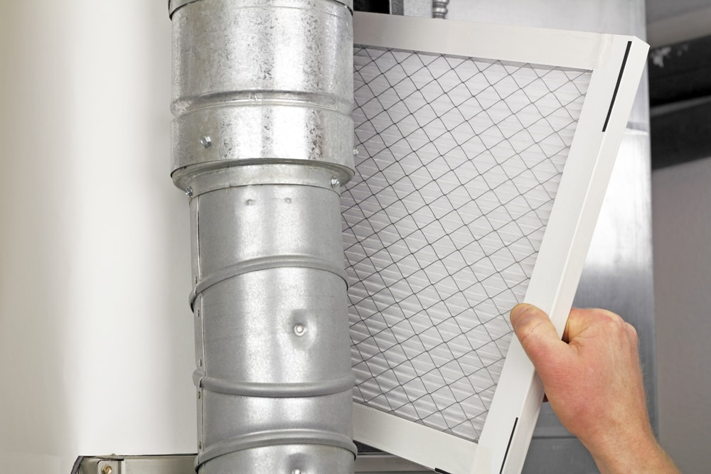 Male arm and hand placing disposable air filter in residential air furnace.