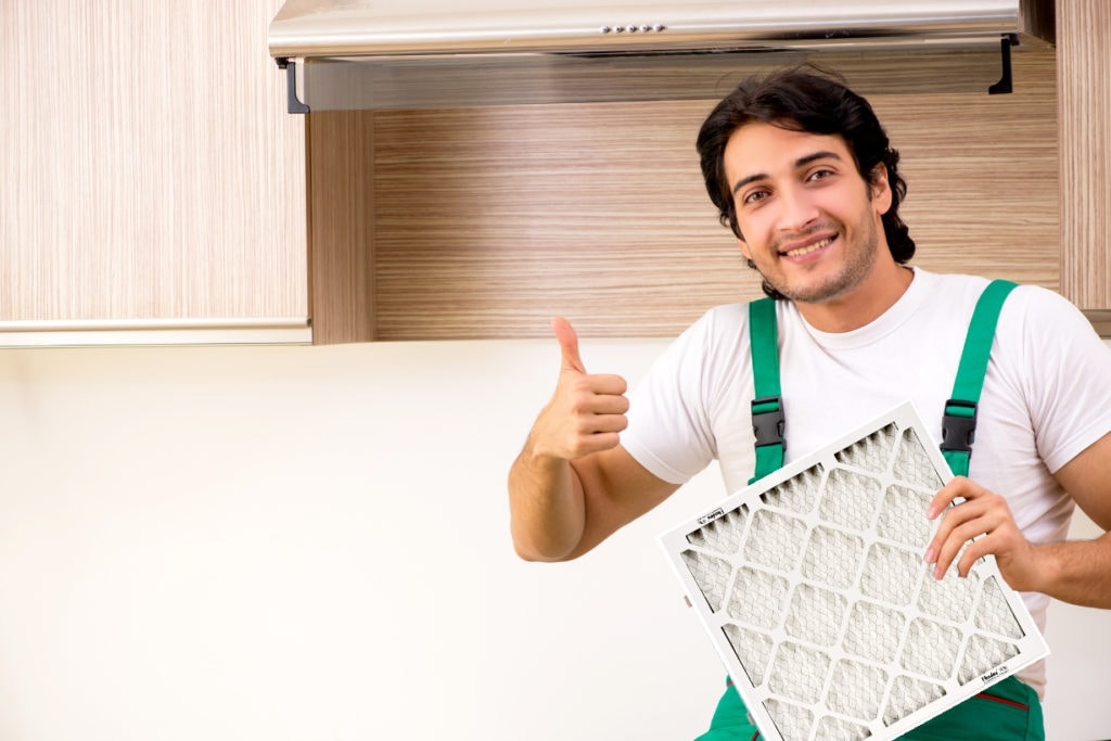 Man holding furnace filter doing thumbs up