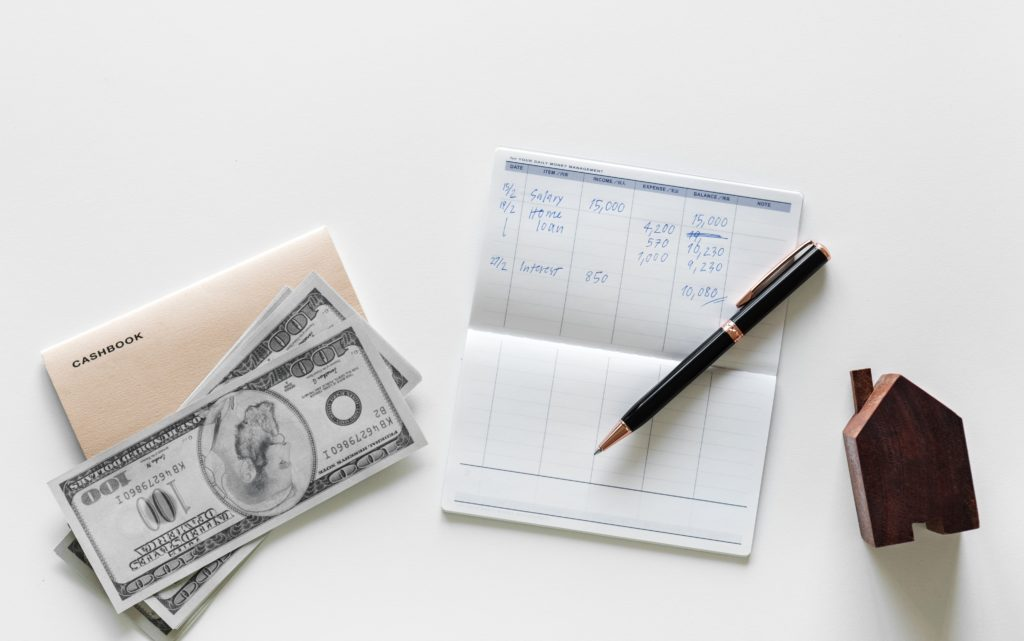Saving, computing, budgeting money with paper cash, ballpen and notebook