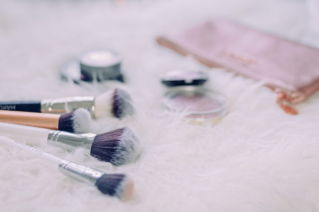 Cosmetics with brushes in pink background