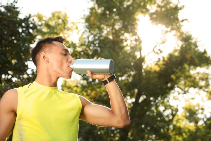 Sporty man drinking from water bottle at park on sunny day.