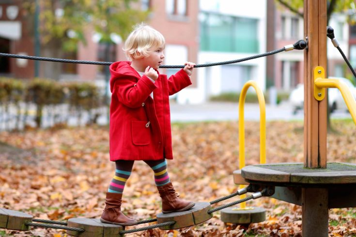 Happy active little child, blonde curly toddler girl wearing beautiful red duffle coat, having fun at playground in the park on sunny autumn day