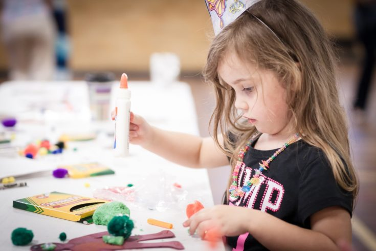little girl making handcraft at a table at a kids party