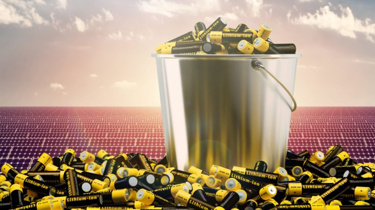 Bucket of Lithium-ion AA Batteries in front of a Solar Energy Plant background