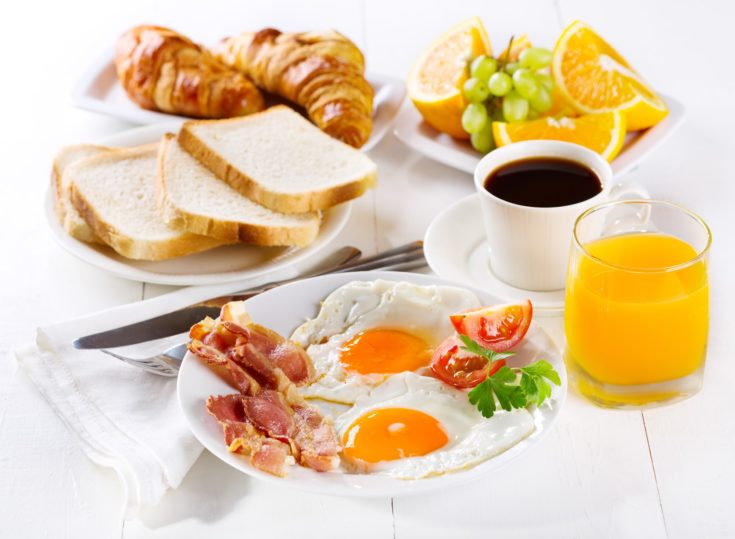 breakfast with fried eggs, croissants, juice, coffee and fruits