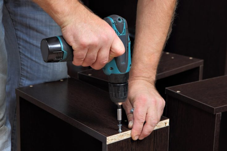 Assembling furniture, Hands of a carpenter with a electric Cordless screwdriver, tighten the screw in drawers of chipboard.