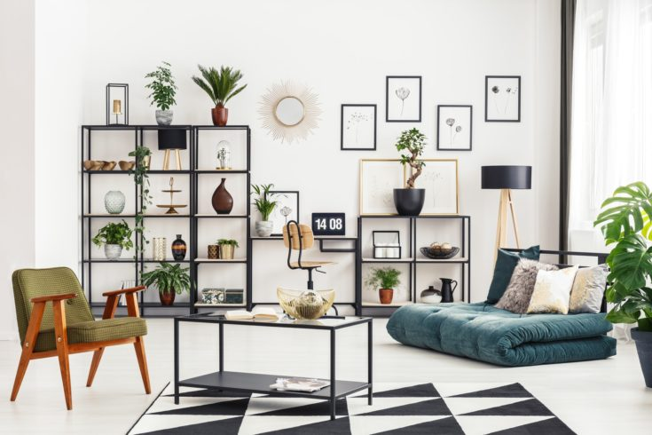 Home office corner with desk and laptop in white living room interior with folded mattress sofa, fresh plants and metal rack